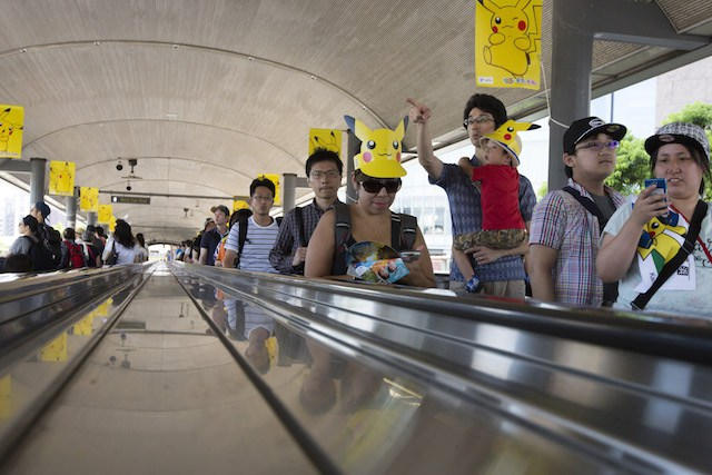 YOKOHAMA, JAPAN - AUGUST 07:  (EDITORIAL USE ONLY) People wearing Pikachu shaped sun visors ride on a moving walkway as they arrive for the Pikachu Outbreak event hosted by The Pokemon Co. on August 7, 2016 in Yokohama, Japan. A total of 1, 000 Pikachus appear at the city's landmarks in the Minato Mirai area aiming to attract visitors and tourists to the city. The event will be held through Aug. 14.  (Photo by Tomohiro Ohsumi/Getty Images)