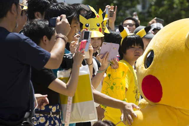 YOKOHAMA, JAPAN - AUGUST 07:  (EDITORIAL USE ONLY) People take photographs of performers dressed as Pikachu, a character from Pokemon series game titles, marching during the Pikachu Outbreak event hosted by The Pokemon Co. on August 7, 2016 in Yokohama, Japan. A total of 1, 000 Pikachus appear at the city's landmarks in the Minato Mirai area aiming to attract visitors and tourists to the city. The event will be held through Aug. 14.  (Photo by Tomohiro Ohsumi/Getty Images)