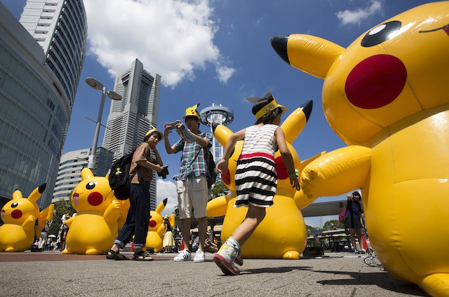 YOKOHAMA, JAPAN - AUGUST 07:  (EDITORIAL USE ONLY)  A girl runs past Pikachu shaped balloons as a couple takes a photograph during the Pikachu Outbreak event hosted by The Pokemon Co. on August 7, 2016 in Yokohama, Japan. A total of 1, 000 Pikachus appear at the city's landmarks in the Minato Mirai area aiming to attract visitors and tourists to the city. The event will be held through Aug. 14.  (Photo by Tomohiro Ohsumi/Getty Images)