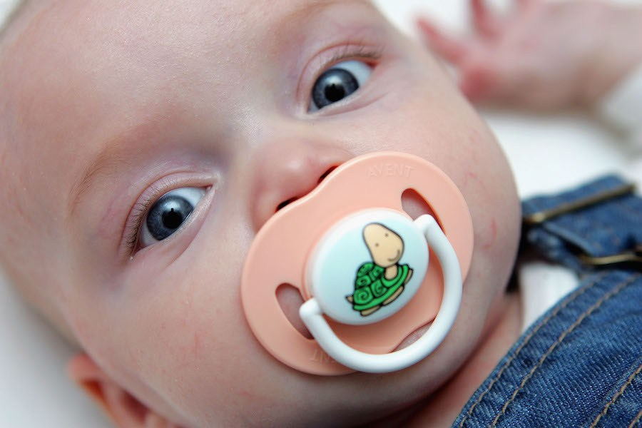 LONDON - DECEMBER 09:  In this photo illustration a baby suckles a dummy whilst resting in her cot on December 09, 2005 in London, England. A recent US study has shown that cot deaths can be reduced by 90 percent if a baby sleeps with a dummy.  (Photo by Daniel Berehulak/Getty Images)