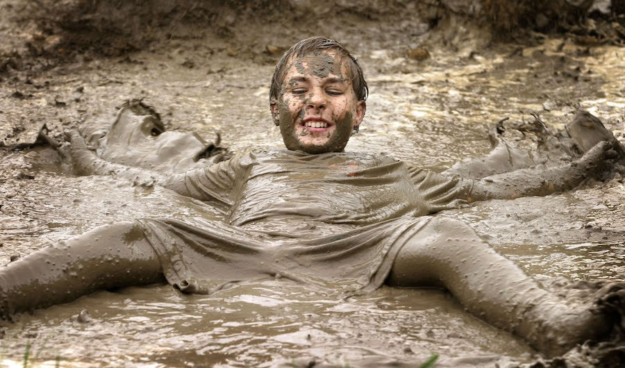 """WESTLAND, MI - JULY 6:  John Irwin, age 12, of Livonia, MIchigan makes a """"mud angel"""" at Westland's Annual Mud Day July 6, 2004 in Westland, Michigan. The popular event brings together several hundred children, 20,000 gallons of water and 200 tons of topsoil to make the mud fest. (Photo by Bill Pugliano/Getty Images)"""